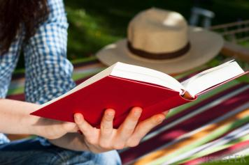 person-reading-red-covered-book-near-grass.jpg
