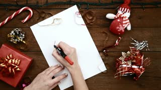 young-woman-sitting-at-wooden-table-writing-letter-to-santa-at-christmas-holiday-concept-of-new-year-magic-dream-and-tradition_rhd33ygge_thumbnail-small01