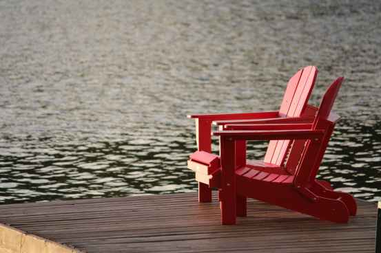 red wooden lounge chair on brown boardwalk near body of water during daytime