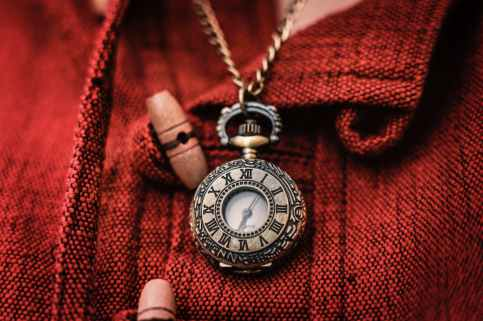 gold colored chain necklace with watch pendant