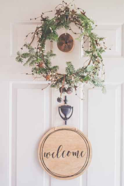 photo of a white door with a hanging wreath and welcome decor