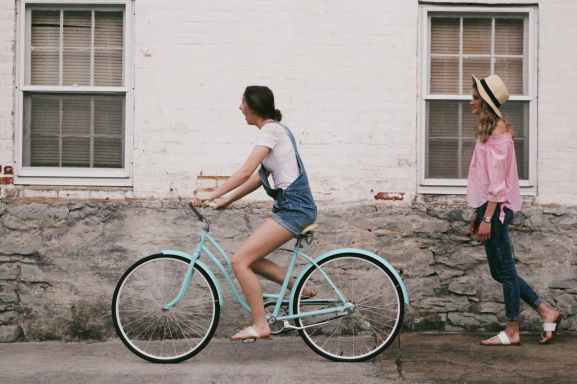 woman riding on teal cruiser bike near woman wearing pink long sleeved shirt