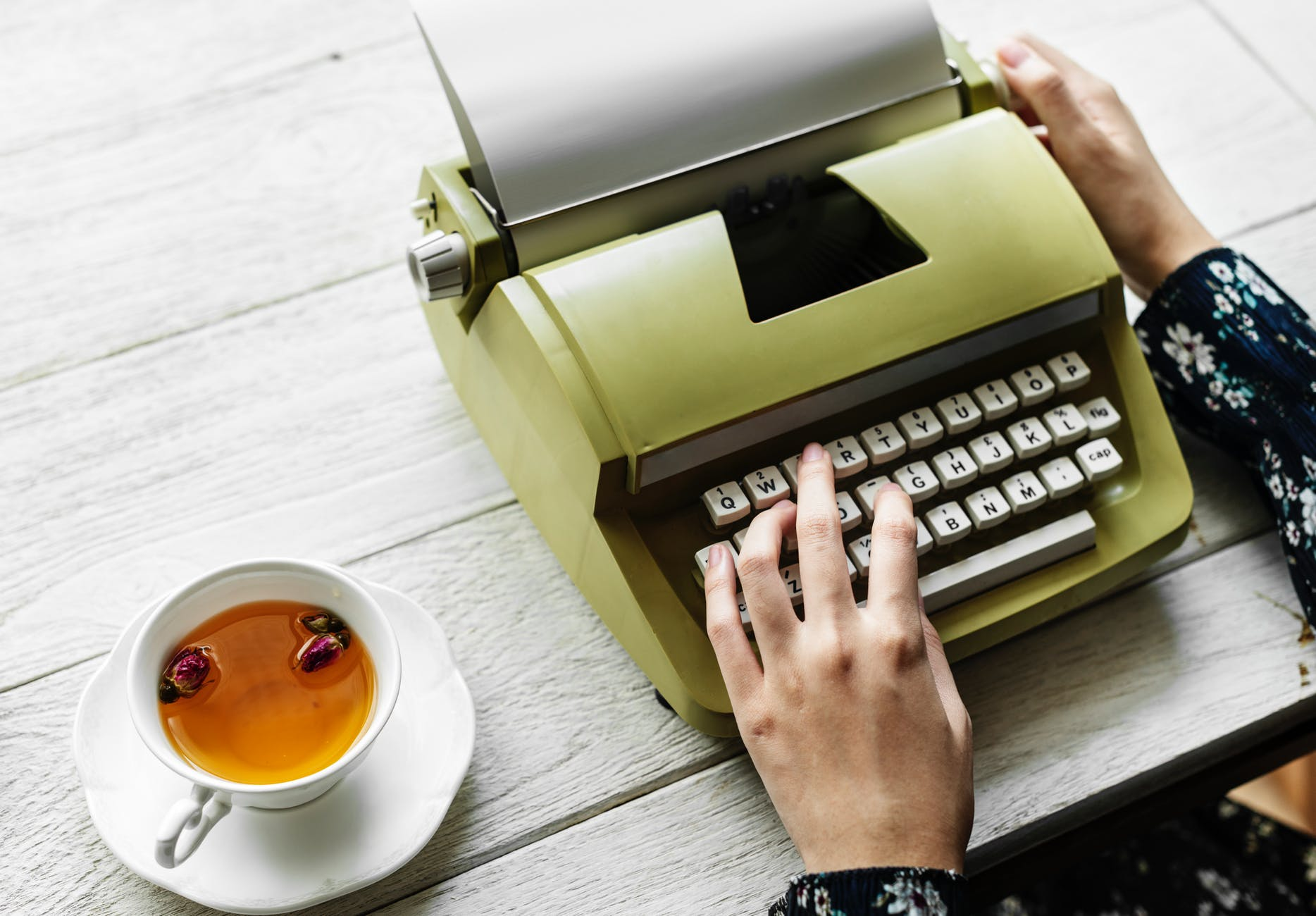 person holding type writer beside teacup and saucer on table