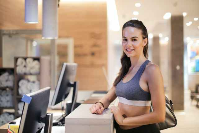 content athletic female at reception desk in sports center