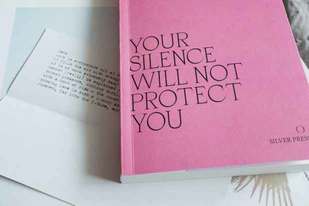 pink book lying above letters on bed