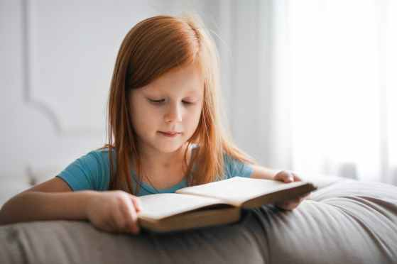 girl in blue t shirt reading book