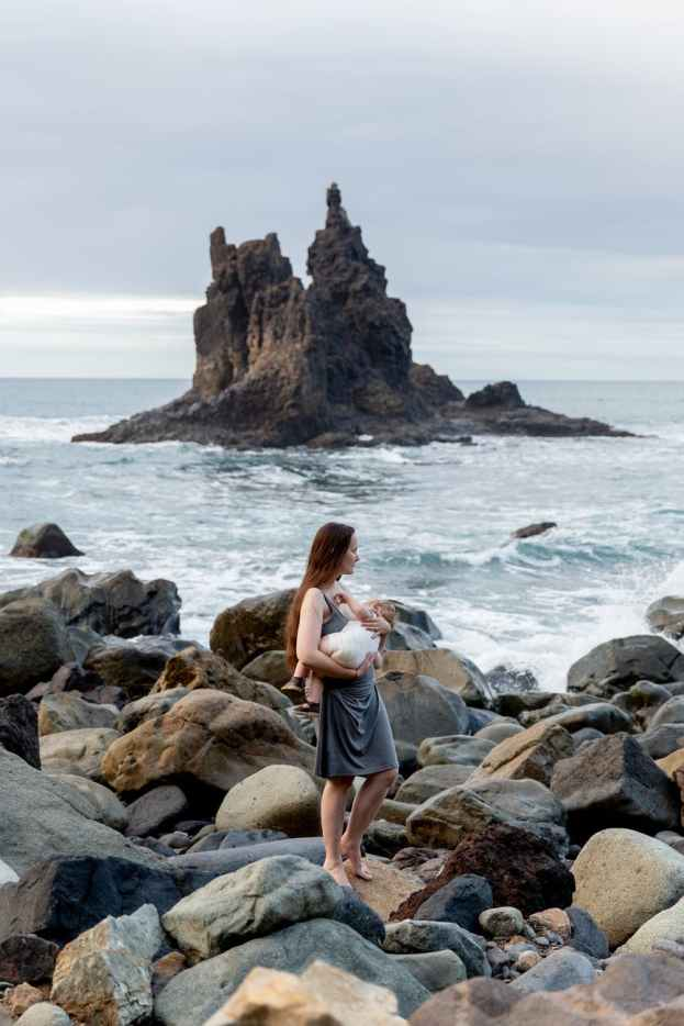 young mother with little baby on hand while standing on rocky seashore