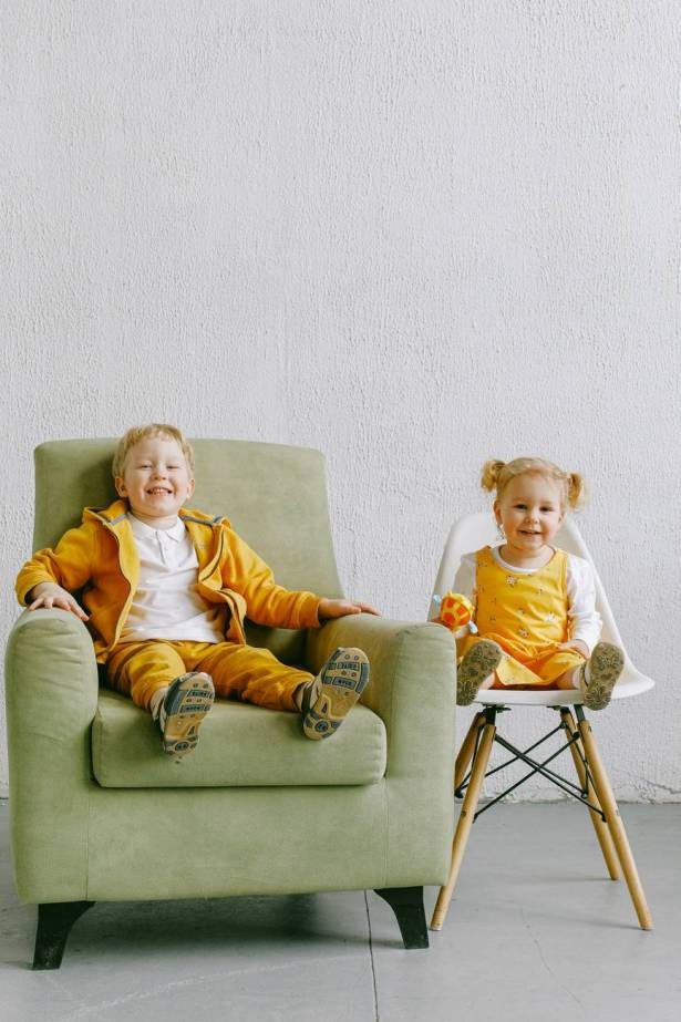 delighted little siblings sitting in living room together