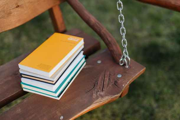 stack of books placed on seat of wooden swing