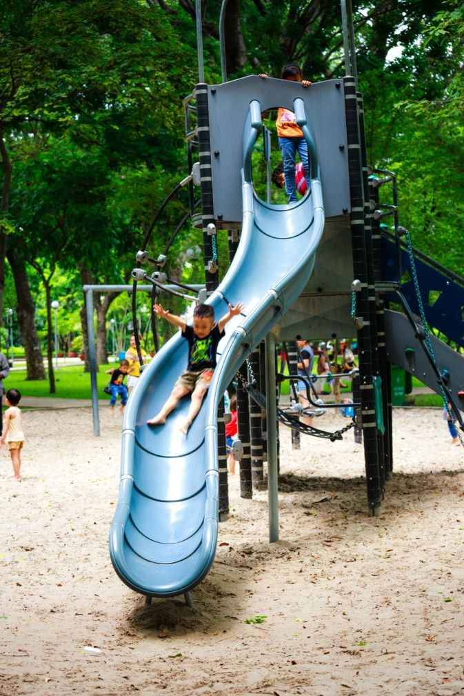 boy playing on slide in playground