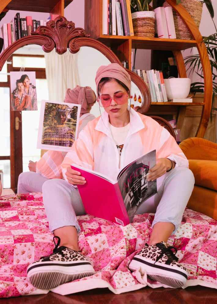 photo of woman sitting while reading a magazine