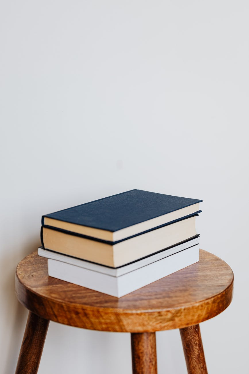 pile of books on wooden stool