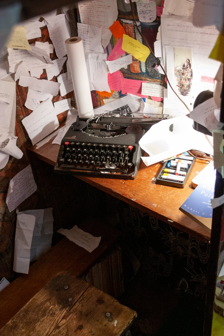 cluttered cramped workplace with typewriter papers