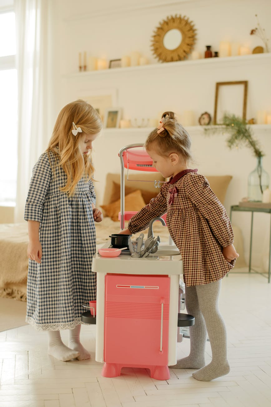 photo of kids playing with kitchen plastic toy