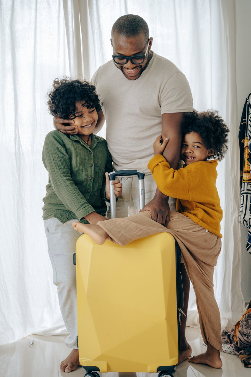 cheerful father with kids and suitcase