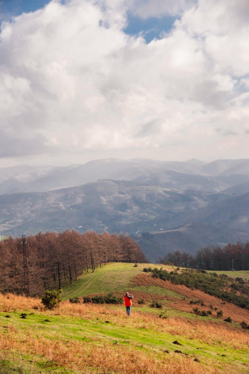 lonely traveler on hillside under cloudy sky