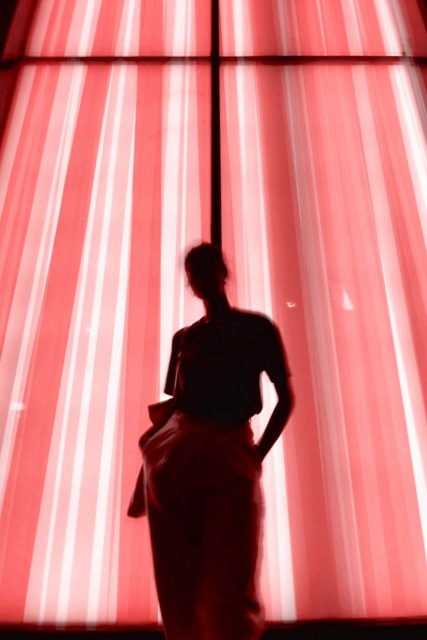 woman standing beside window with pink curtain