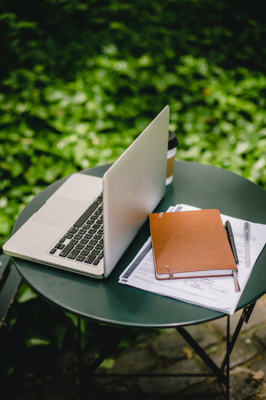 laptop and documents on table in garden