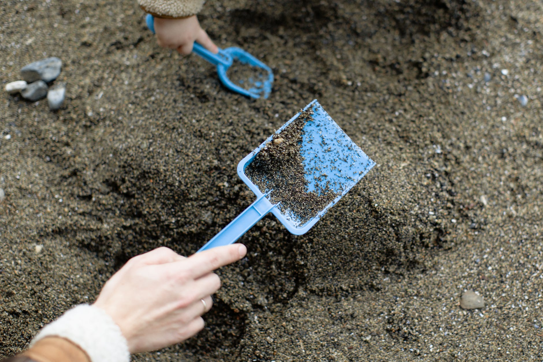 crop faceless mother with baby playing with plastic shovels in sand